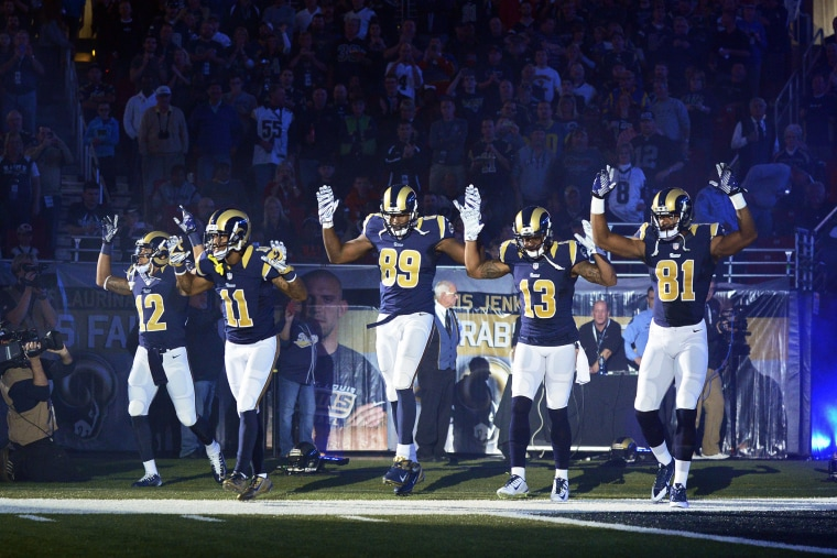 Players on the St. Louis Rams put their hands up to show support for Michael Brown before a game on Nov. 30, 2014 in St. Louis, Mo. (Photo by Jeff Curry/USA Today Sports/Reuters)