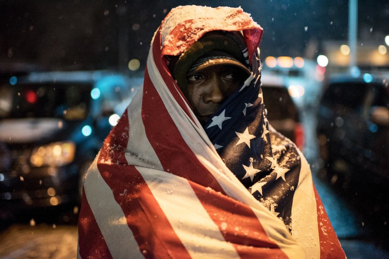 A protester covered in a U.S. flag stands in front of Ferguson Police Department as the snow falls, in Ferguson, Mo. on Nov. 26, 2014. (Photo by Alexey Furman/EPA)