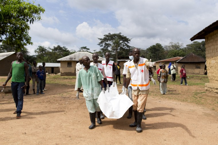 Health workers from Guinea's Red Cross carry the body of a victim of the Ebola virus in Momo Kanedou in Guinea on Nov. 19, 2014. (Photo by Kenzo Tribouillard/AFP/Getty)