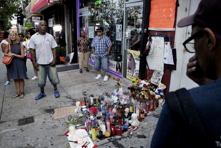 Pedestrians stand beside a memorial for Eric Garner, a Staten Island man who died while being arrested by New York City police, Tuesday, July 22, 2014, in...