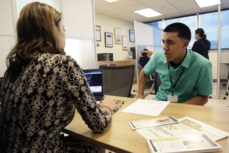 Navigator Dianelys Dominguez, left, assists Giovanny Vega, 18, of Miami, right, sign up for health insurance under the Affordable Care Act, Nov. 17, 2014, in Miami, Fla. (Photo by Lynne Sladky/AP)
