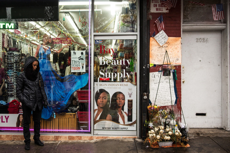 People stand around outside the beauty salon where Eric Garner was killed on July 17, Dec. 3, 2014 in the Staten Island borough of New York, N.Y. (Photo by Andrew Burton/Getty)