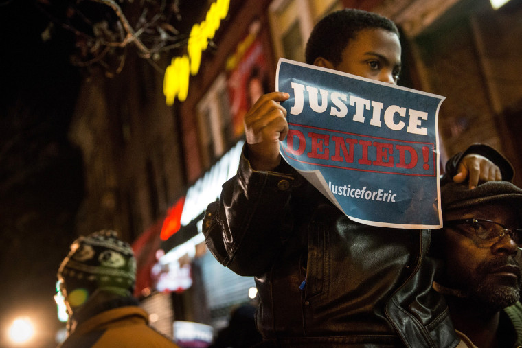 Demonstrators hold an impromptu vigil for Eric Garner, the man killed by a police officer in July using a chokehold, outside the beauty salon where the confrontation took place on Dec. 3, 2014 in the Staten Island borough of New York City.