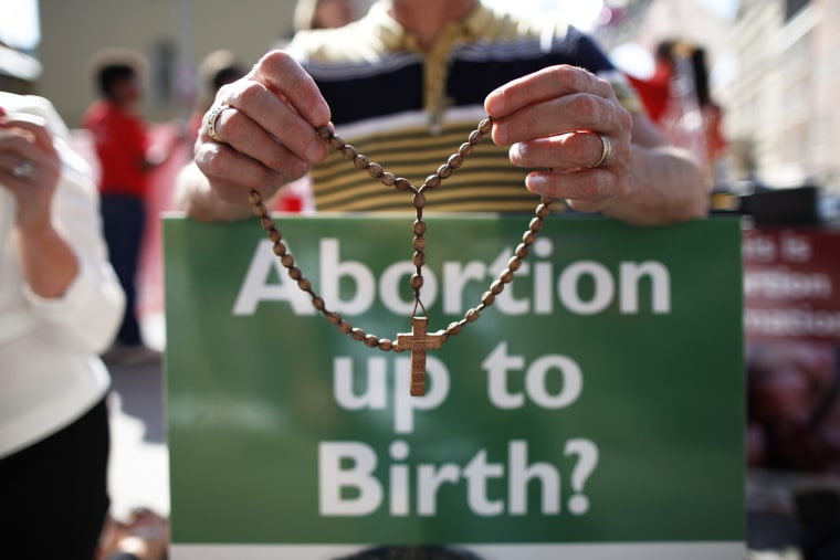 A protester holds rosary beads with a anti-abortion placard. (Photo by Peter Muhly/AFP/Getty)
