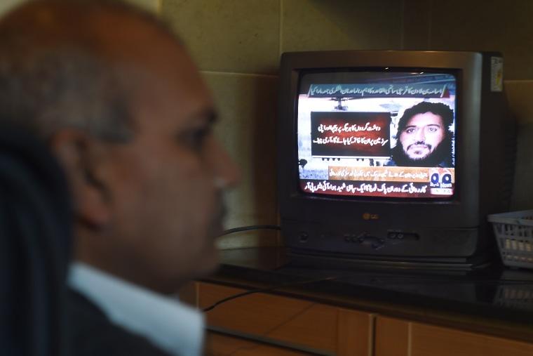A Pakistani man watches a television broadcasting news of top Al-Qaeda leader Adnan El Shukrijumah, in Islamabad on Dec. 6, 2014. (Farooq Naeem/AFP/Getty)