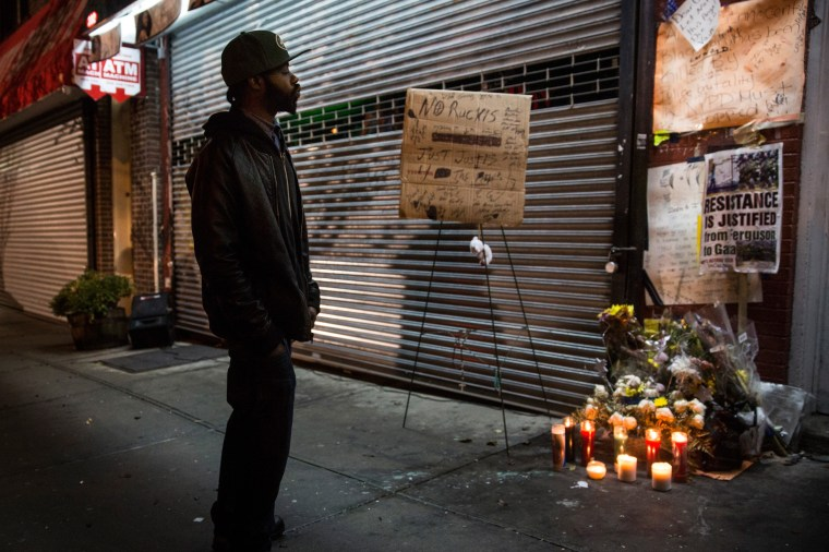 A man pauses at an makeshift memorial for Eric Garner, the man killed by a police officer in July using a chokehold, outside the beauty salon where the confrontation took place, on Dec, 3, 2014 in Staten Island. (Andrew Burton/Getty)