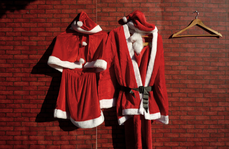 Santa Claus costumes, for a man and woman, hang on the front of a Christmas decorations stall at a market. (Photo by David Gray/Reuters)