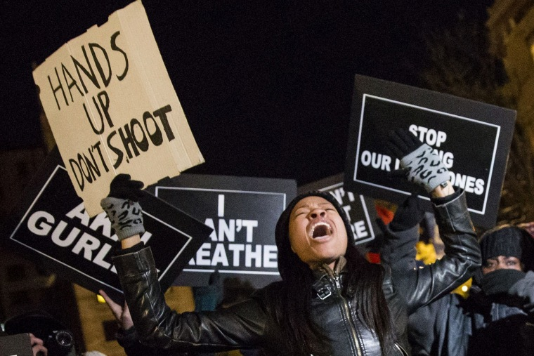A protester, demanding justice for the death of Eric Garner, Michael Brown and Akai Gurley, shouts slogans while holding a placard as she takes part in march through Manhattan, New York on Dec. 7, 2014.
