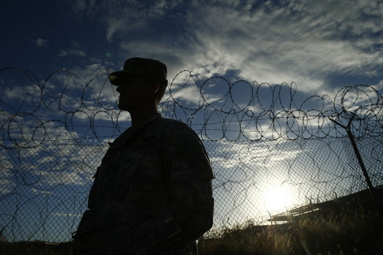In this photo reviewed by the U.S. military, a soldier stands at the now closed Camp X-Ray, which was used as the first detention facility for al-Qaida and Taliban militants who were captured after the Sept. 11 attacks at Guantanamo Bay Naval Base, Cuba on Nov. 21, 2013.