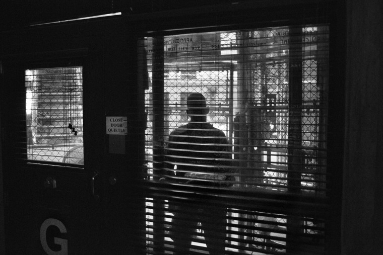Views through the fenced-in guard post into the common area of a cell block in Camp 6 of Guantanamo Bay in 2012. (Photo by Paolo Pellegrin/Magnum Photos)