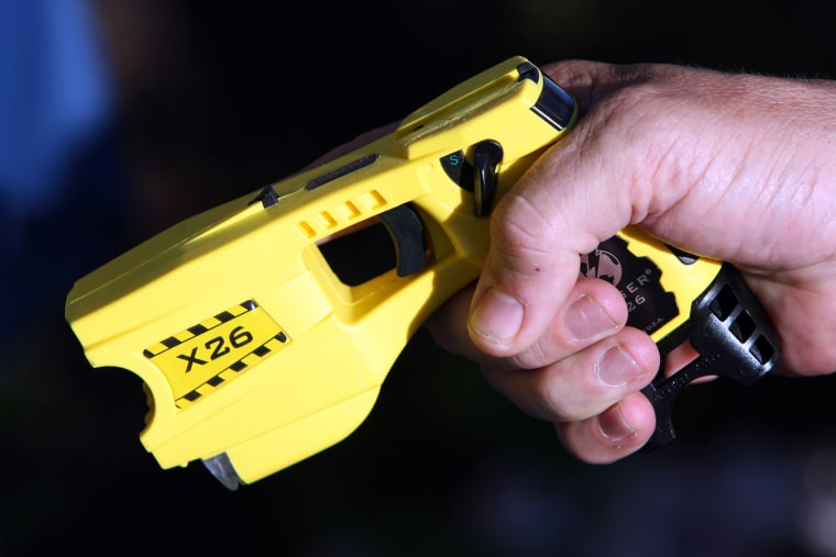 A police officer poses with a taser. (Photo by Sebastien Nogier/Reuters)