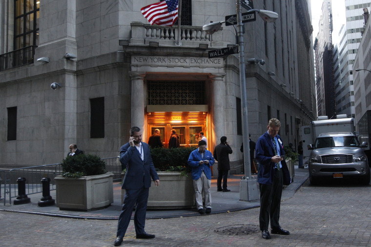 Traders stand outside the New York Stock Exchange prior to the opening bell.