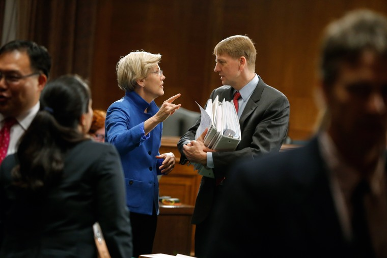 U.S. Senator Warren talks with U.S. Consumer Financial Protection Bureau Director Cordray after he testified about Wall Street reform before a Senate Banking Committee hearing on Capitol Hill in Washington