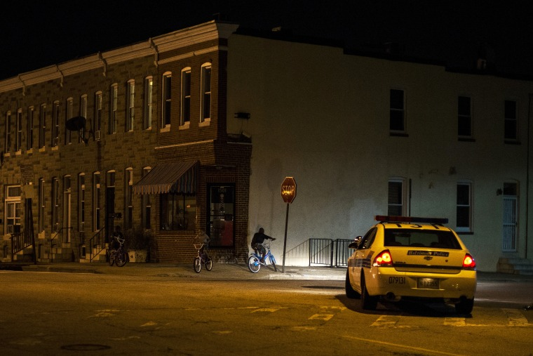 Police patrol a residential neighborhood in east Baltimore minutes after a curfew law took effect in Baltimore
