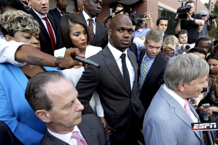 Minnesota Vikings running back Adrian Peterson, center, stands outside the courthouse after making his first court appearance, Oct. 8, 2014, in Conroe, Texas. (Photo by David J. Phillip/Pool/AP)