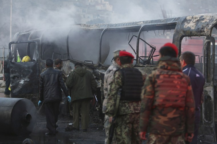 Afghan security guards inspect a damaged bus at the site of a suicide attack by the Taliban in Kabul, Afghanistan on Dec. 13, 2014. (Rahmat Gul/AP)