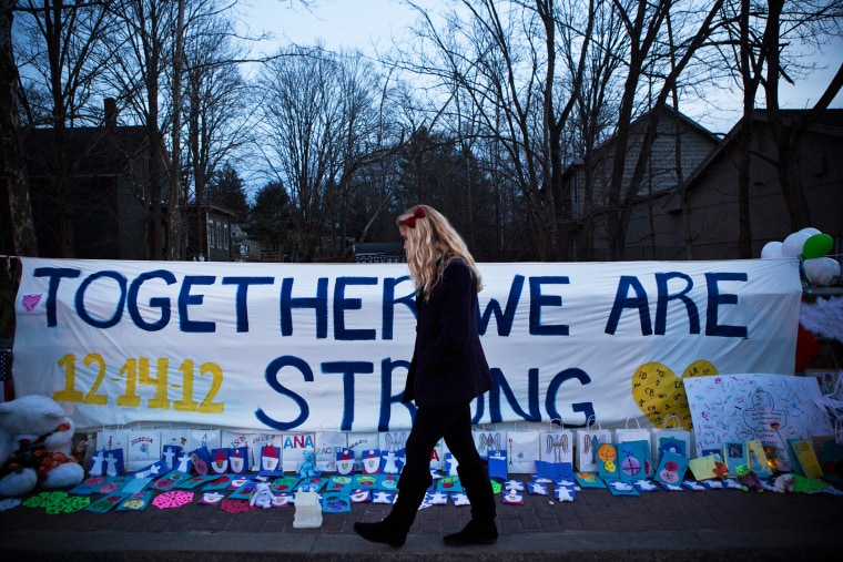 """A woman walks past a sign that reads \""""Together we are Strong\"""" at a memorial for those killed in the school shooting at Sandy Hook Elementary School on Dec. 24, 2012 in Newtown, Conn. (Photo by Andrew Burton/Getty)"""