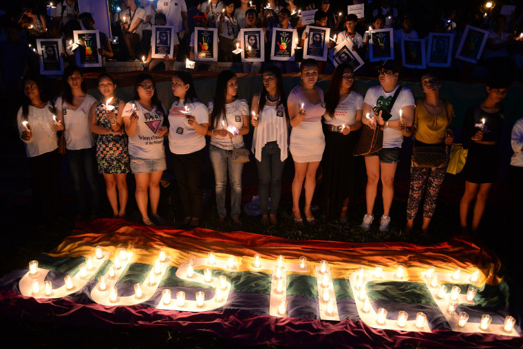 Protesters hold candles during a vigil inside the campus of the state university in Manila on Oct. 24, 2014, to coincide with the burial of murdered transgender woman, Jennifer Laude. (Photo by Ted Aljibe/AFP/Getty)