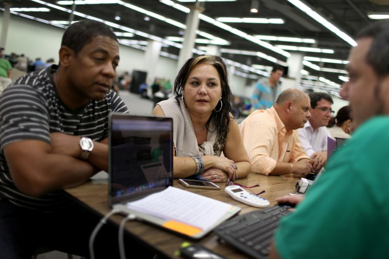 Jose Ramirez and Mariana Silva speak with Yosmay Valdivia, an agent from Sunshine Life and Health Advisors, as they discuss plans available from the Affordable Care Act on Dec. 15, 2014 in Miami, Fla. (Joe Raedle/Getty)