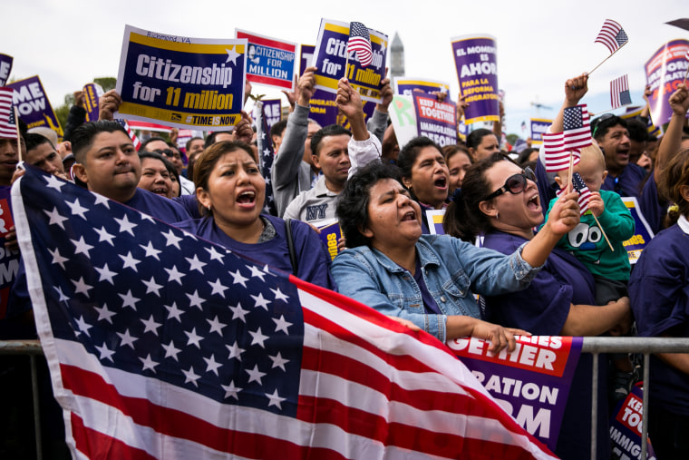 Lorena Ramirez, of Arlington, Va., holds up an American flag as she cheers with her friend Lilia Beiec during a rally in support of immigration reform on Oct. 8, 2013 in Washington, DC. (Drew Angerer/Getty)