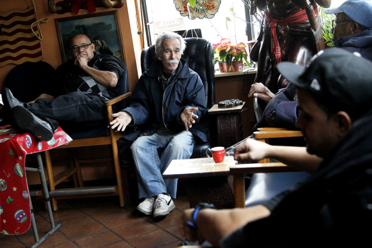 Roberto Martinez Gonzalez, 73, second from left, an former Cuban national who left his birth country during the El Mariel exodus, talks to Manuel Lopez, Juan Perez and Tony Montalvo regarding Cuba at a cigar shop on Dec. 17, 2014, in Union City, N.J.
