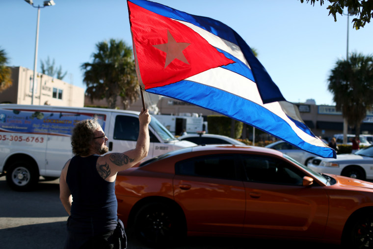 \Abdel Rodriguez holds a Cuban flag as he stands outside the Little Havana restaurant Versailles on Dec. 17, 2014 in Miami, Fla. (Joe Raedle/Getty)