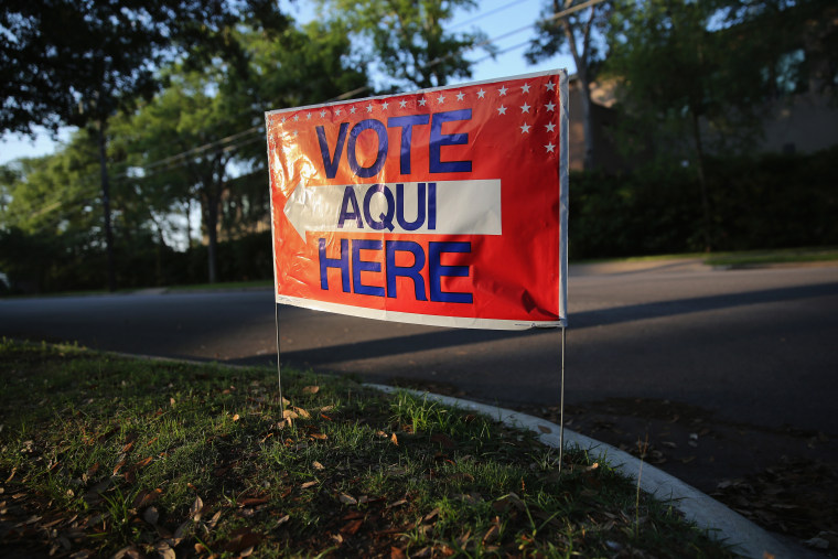 A bilingual sign stands outside a polling center at public library ahead of local elections on April 28, 2013 in Austin, Texas. (John Moore/Getty)