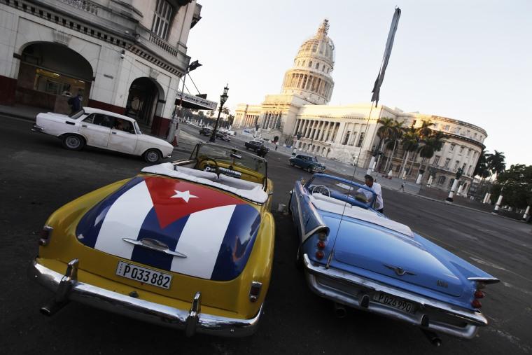 A car with a Cuban flag is parked near Cuban Capitol in Havana on Dec. 18, 2014. (Photo by Enrique de la Osa/Reuters)
