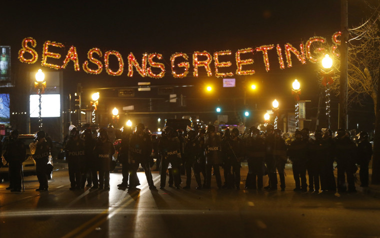 Police form a line in the street under a holiday sign after a grand jury returned no indictment in the shooting of Michael Brown in Ferguson, Missouri