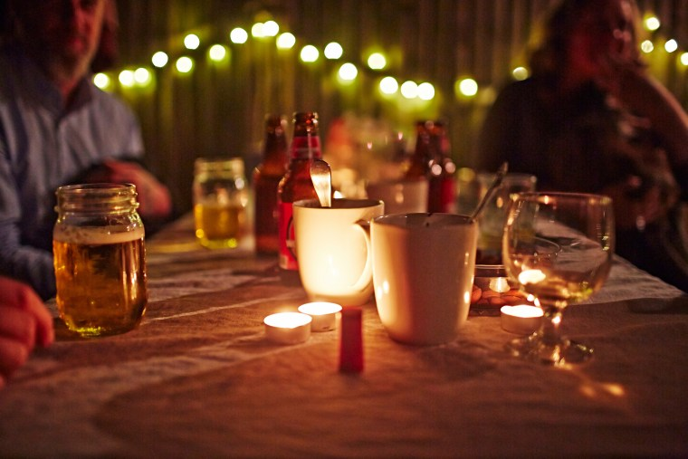 People sitting at table with candles and drinks.
