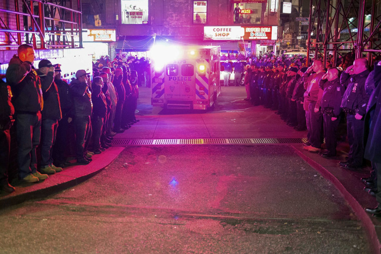 Police officers salute as vehicles containing the bodies of two New York Police officers who were shot dead drive by in Brooklyn on Dec. 20, 2014. (Stephanie Keith/Reuters)