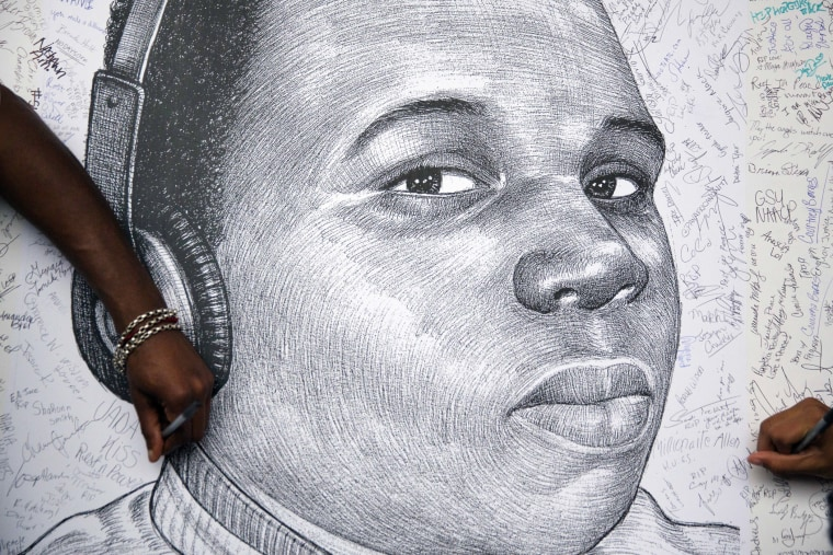 Protestors autograph a sketch of Michael Brown during a protest, Monday, Aug. 18, 2014, in Atlanta, Ga. (Photo by David Goldman/AP)