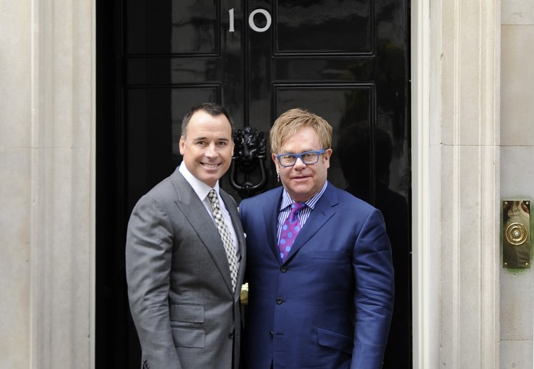 British entertainer Elton John poses for photographs with his partner David Furnish outside 10 Downing Street before a meeting with Prime Minister David Cameron in London
