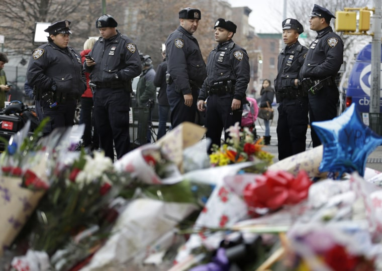 New York City police officers gather near a makeshift memorial near the site where fellow officers Rafael Ramos and Wenjian Liu were murdered in the Brooklyn borough of New York, Dec. 22, 2014.