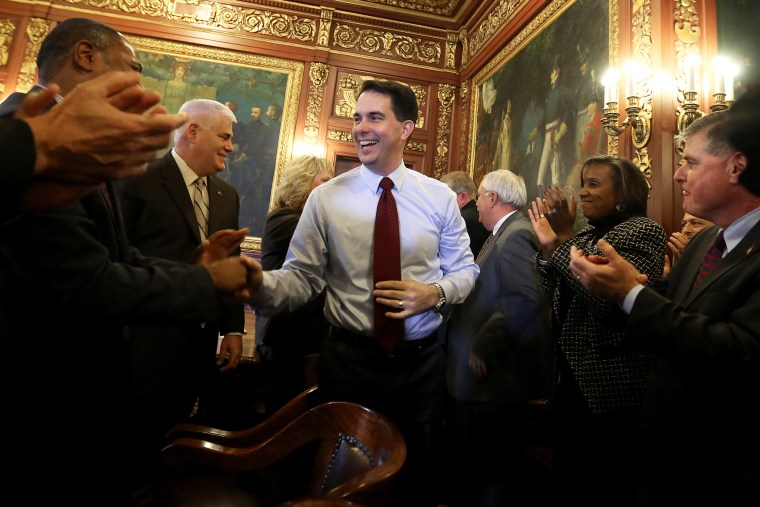 Wisconsin Republican Gov. Scott Walker is greeted by members of his staff and cabinet at the Wisconsin State Capitol building in Madison, Wis., Nov. 5, 2014. (Photo by John Hart/Wisconsin State Journal/AP)