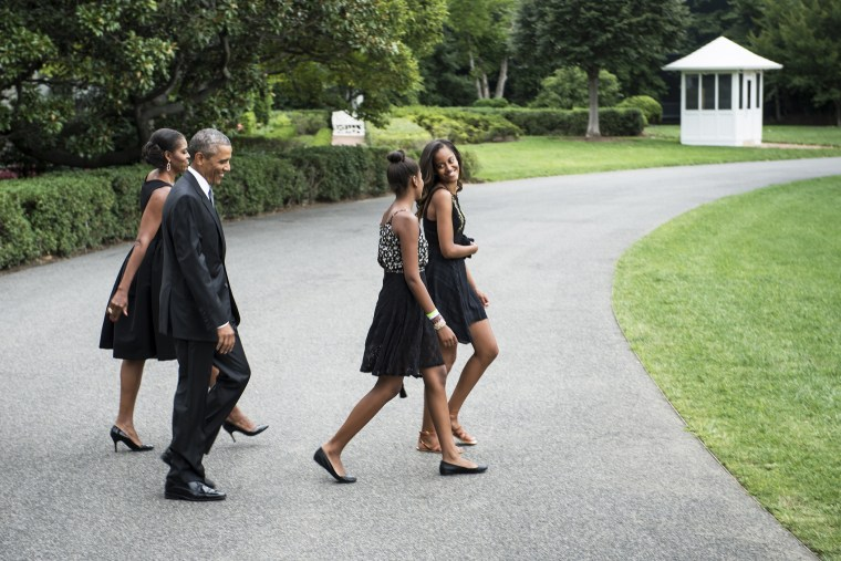 US President Barack Obama (2L) and US First Lady Michelle Obama (L) catch up to their daughters Sasha (2R) and Malia while walking to Marine One on the South Lawn of the White House on Aug. 30, 2014 in Washington, DC.