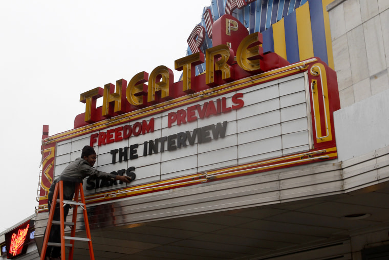 "General Manager Delaney puts letters on the marquee sign after the announcement that the Plaza Theatre would be showing the movie ""The Interview"" in Atlanta"