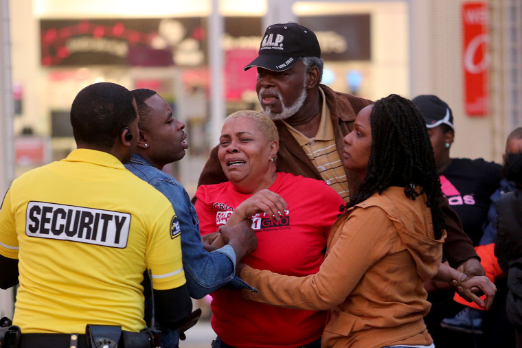 A distraught woman is comforted outside the food court entrance to Oakwood Mall after a fatal Christmas Eve shooting inside the Foot Locker on Dec. 24, 2014.