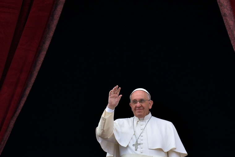 """Pope Francis salutes as he gives his traditional Christmas \""""Urbi et Orbi\"""" blessing from the balcony of St. Peter's Basilica on Dec. 25, 2014 at the Vatican."""