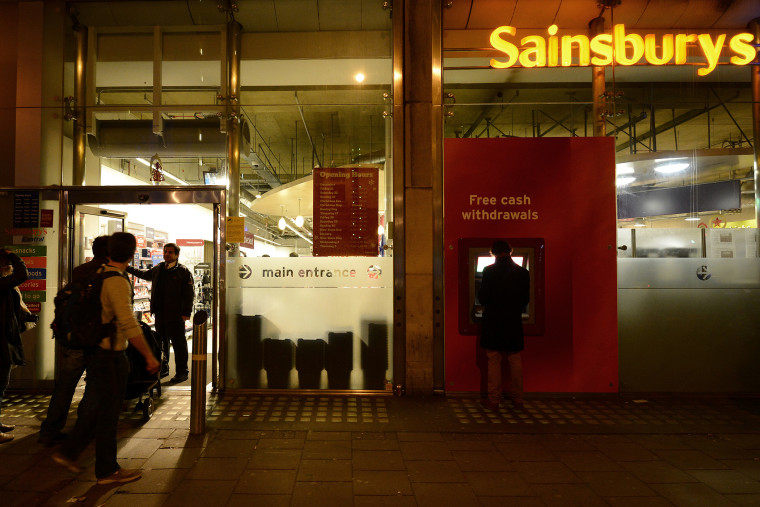 A security guard locks the door to a Sainsbury store in central London on Dec. 23, 2012.