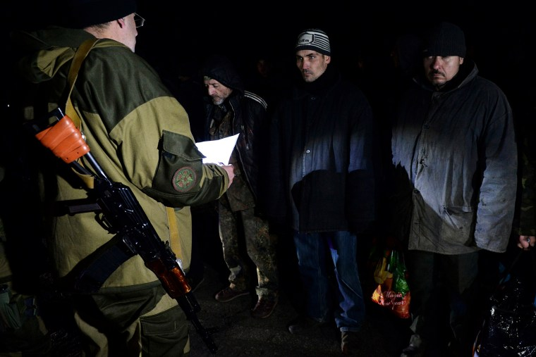 Ukrainian prisoners stand as a pro-Russian rebel holds a sheet of paper during procedures for a prisoner exchange with Ukraine on Dec. 26, 2014 in the eastern Ukrainian city of Yasinovataya, near Donetsk.