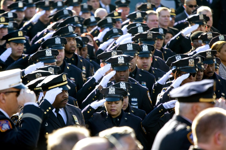 Thousands of police officers and others salute during the National Anthem as the funeral of New York City police officer Rafael Ramos begins at Christ Tabernacle Church in the Glendale section of Queens, where he was a member, Dec. 27, 2014, in New York.