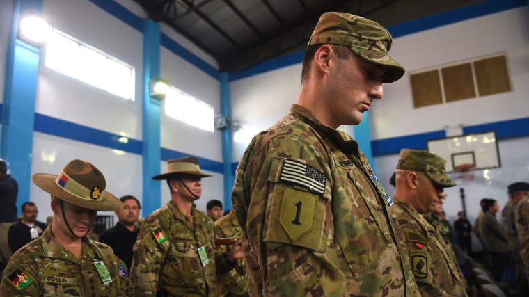 NATO-led International Security Assistance Force (ISAF) bow their heads during a ceremony marking the end of ISAF's combat mission in Afghanistan at ISAF headquarters in Kabul on Dec. 28, 2014. (Photo by Shah Marai/AFP/Getty)
