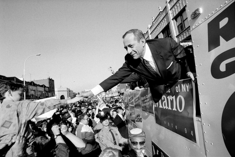 From a campaign bus, Gov. Mario Cuomo of New York shakes hands with supporters on Oct. 30, 1994.