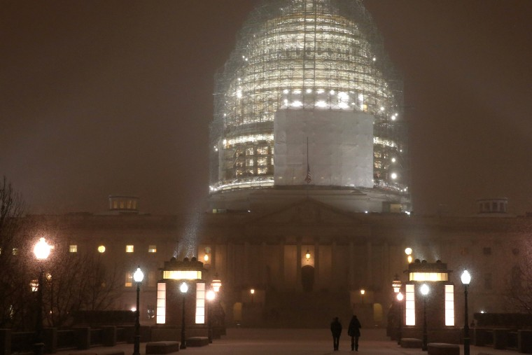 People walk in the falling snow in front of the US Capitol, on Jan. 6, 2015 in Washington, DC.
