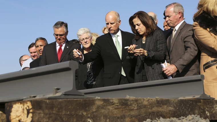 California Governor Jerry Brown (C) and his wife, Anne Gust, prepare to sign a railroad rail during a ceremony for the California High Speed Rail in Fresno, Calif., on Jan. 6, 2015. (Photo by Robert Galbraith/Reuters)
