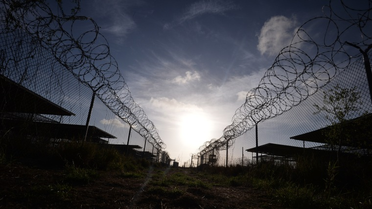"This photo made during an escorted visit and reviewed by the US military, shows the razor wire-topped fence at the abandoned ""Camp X-Ray"" detention facility at the US Naval Station in Guantanamo Bay, Cuba, April 9, 2014. (Photo Mladen Antonov/AFP/Getty)"