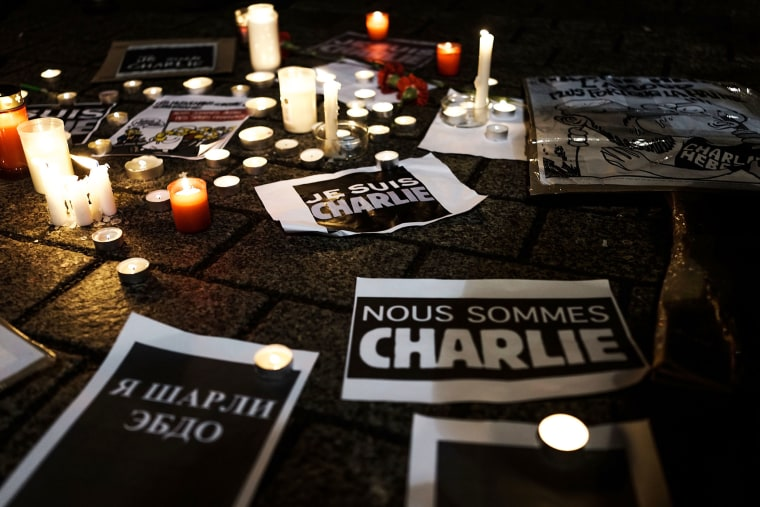 "Papers with the written words ""We are Charlie"" lie on the ground while people gather at a vigil in front of the French Embassy following the terrorist attack in Paris on Jan. 7, 2015 in Berlin, Germany. (Photo by Carsten Koall/Getty)"