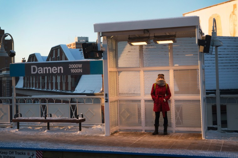 A woman tries to stay warm as she waits for a train on an L platform during the morning rush while temperatures hovered around zero degrees Fahrenheit on January 7, 2015 in Chicago, Illinois. (Photo by Scott Olson/Getty)