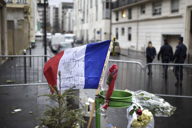 """A French flag reading """"to Liberty"""" is placed near a barrier outside the offices of French satirical newspaper Charlie Hebdo in Paris on Jan. 8, 2015."""